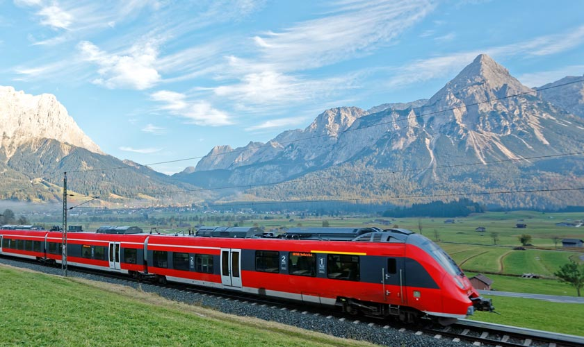 Red electric train traveling passed mountains