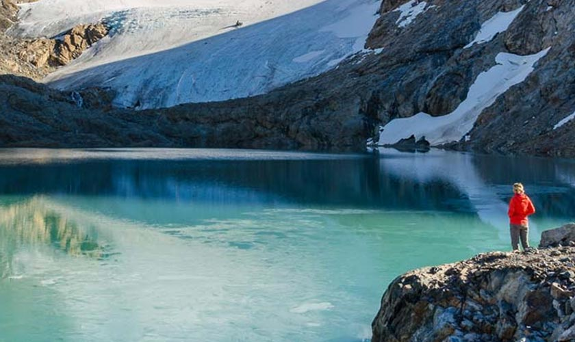 Woman in a red jacket looking at a glacial lake